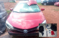 The robbed Toyota corolla involved in an accident. INSET: The items belonging to the armed robbers