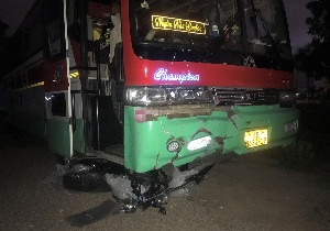 The motorbike still trapped under the bus