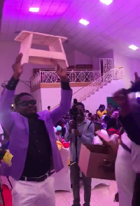 The groom with the kitchen stool presented by his friends