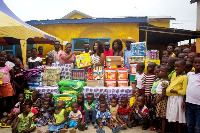 Nana Ama Mcbrown  with Maxwell, others presenting the items to Royal Seed Home and School