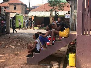 Melphia (left) sitting on the steps of Martin Opoku Sekyere