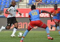 Andre Ayew (L) advances with the ball past DR Congo's midfielder Merveille Merveille Bokadi