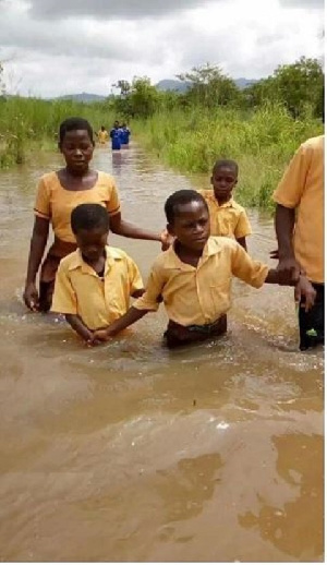 Some students walking through water to school