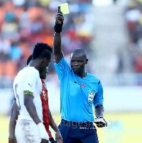 A Mozambican player booked after he hauled down John Boye