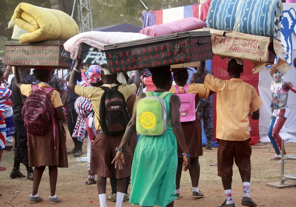 Some high school students on their way to school with luggages
