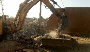 An excavator demolishing a mining pit