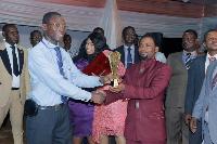 Director Of Administration Cogai,  Elvis Daniels Botchway presenting the trophy to Bismark Amoah