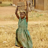 A child carrying cement blocks