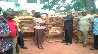 Mr Dennis Armah-Frempong presenting the desk to the schools