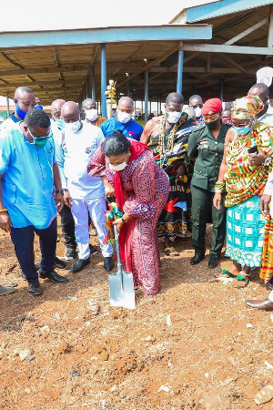 The first lady cutting sod for the construction of a 40-stall market complex at Ningo