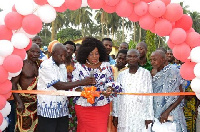 Queenstar Sawyer (M) cutting the tape for the newly built community center at Agona East