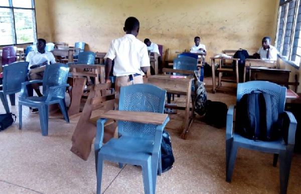 Students who sit in plastic chairs write on their laps