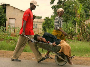 The writer says transporting a sick person in a wheelbarrow throws dust on Africans as non-humans