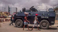 Pedestrians walk past an Angola police armoured personnel carrier seen blocking a street in Luanda