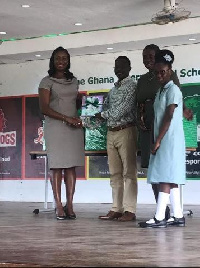 Nadia Bruce-Muller presents books to Mr. Quarmson while Ms Asare and Miss Kyei-Mensah look on