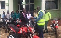 DCE (Right), presenting the keys of one of the motorbikes to the Agric Director