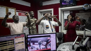 People pray and sing during a worship radio show at Accra FM station in Accra on April 26, 2021