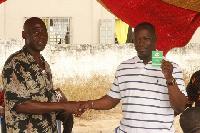 Kofi-Buah receiving his new NDC membership card at a branch meeting