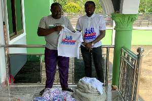 Daniel Otting Awuah presenting the items to Emmanuel Adei Domson