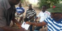 George Kuntu Blankson receiving his party identification card after registering as a member