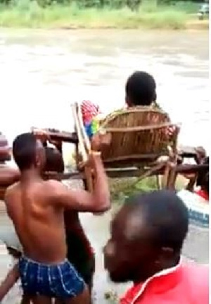 A pregnant woman being carried in a chair across the river