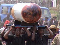 A cigarette-shaped coffin is carried in a funeral procession in the Ghanaian capital, Accra. Relatives wanted to honor the dead man's love of smoking and his cigarette business.