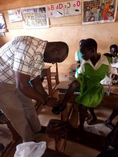 Nzema East MCE donates sandals, shoes to schools
